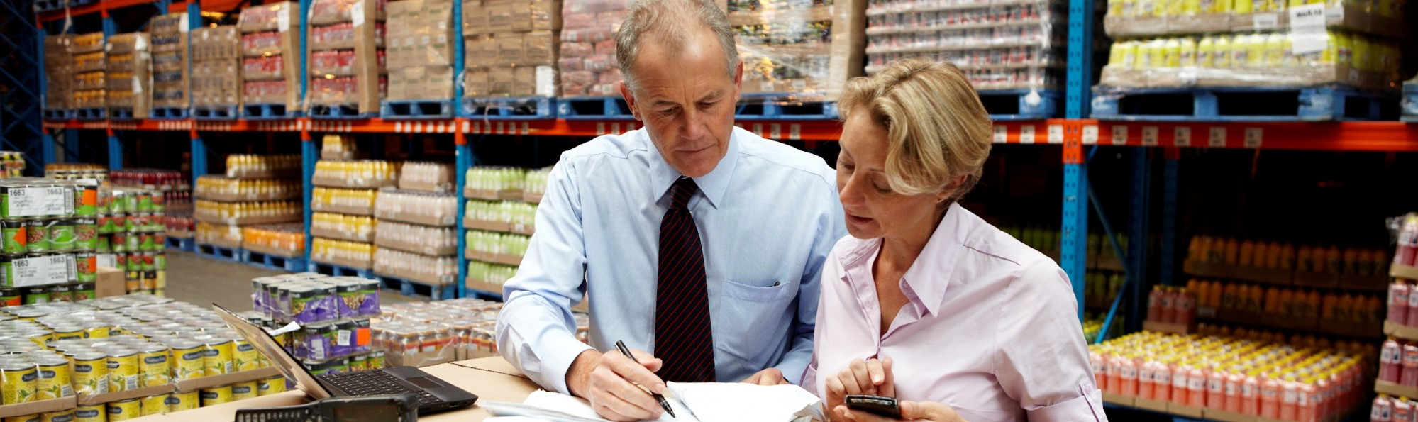 Professional man and woman discuss documents in warehouse