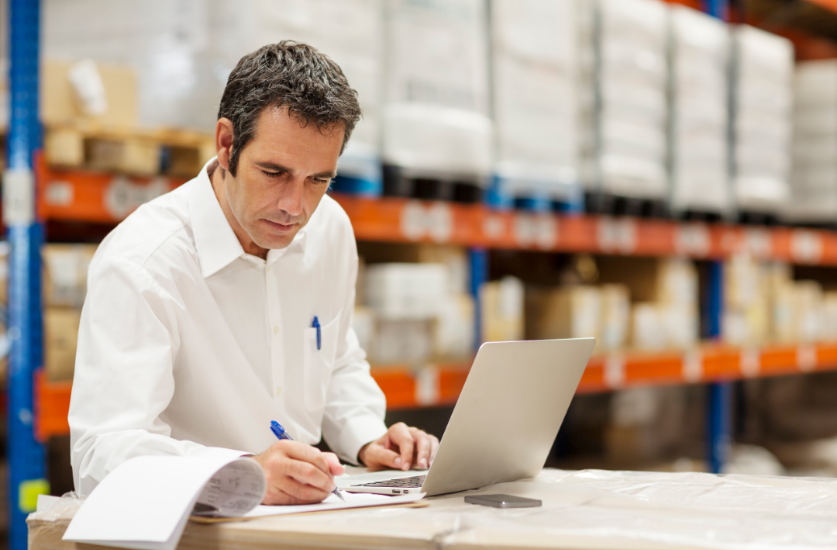 Businessman in warehouse writing down inventory and uploading to computer
