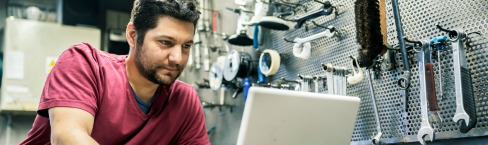 Man on computer surrounded by tools insuring goods