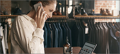 Female clothing retailer stands at counter looking at laptop with phone to ear smiling