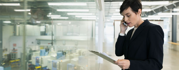 Business woman standing in office setting on the phone