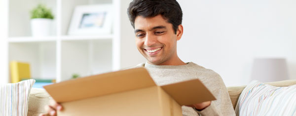 man smiling when opening a package