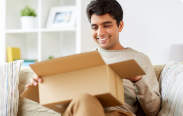 Man sitting on the couch smiling while opening a small cardboard package