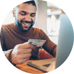 Smiling man about to purchase goods online via credit card